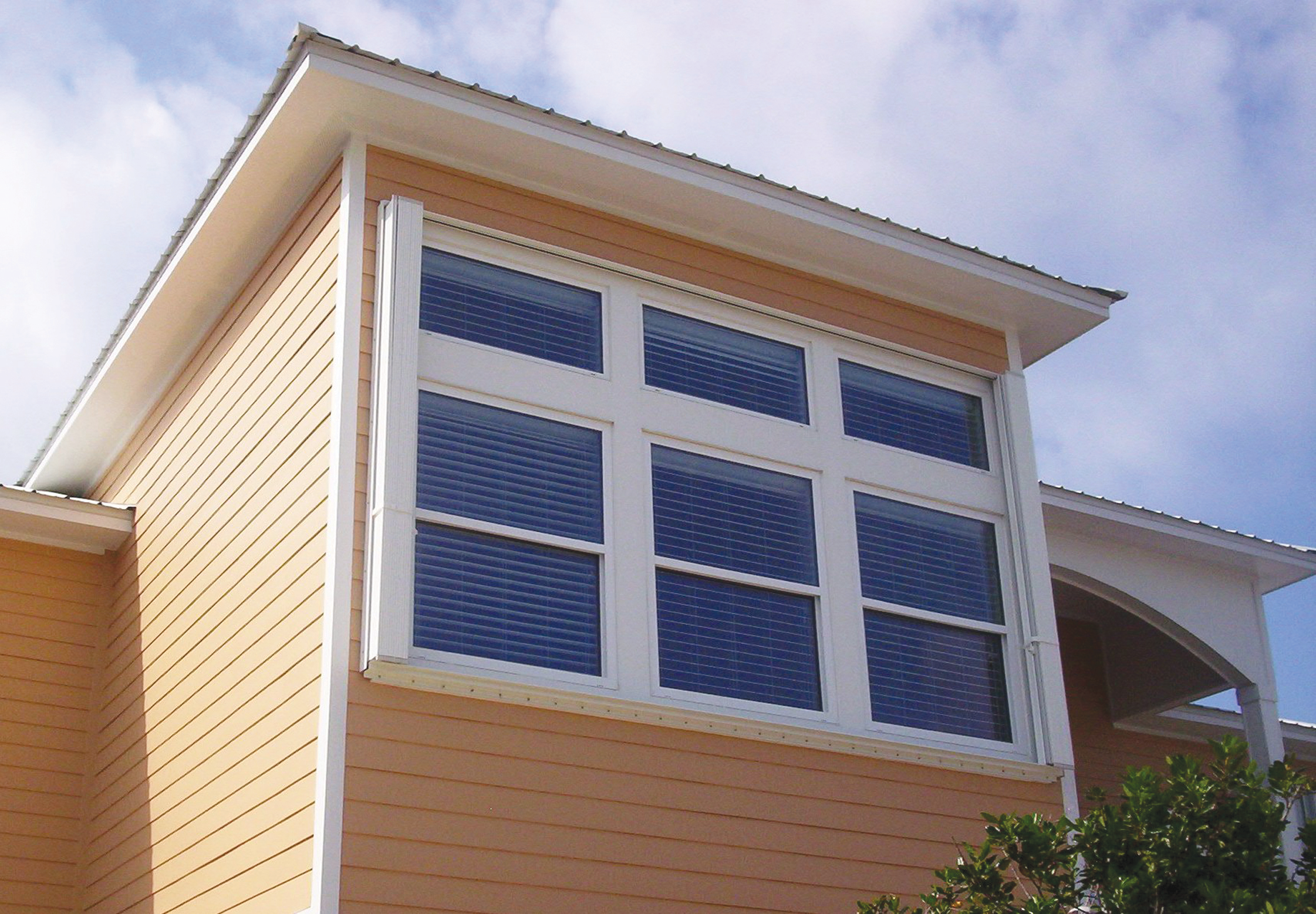 Figure 4-9. Accordion shutter (shown in open position) installed over a large window group of a coastal home. Shutter has been installed to allow deployment from inside the home.  Source: Roll-a-way/QMI.
